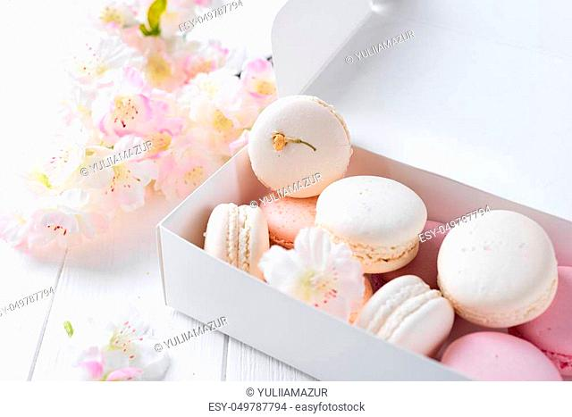 Tender pink and white macarons on white wooden background