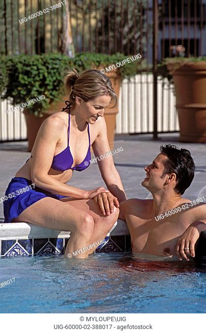A couple enjoy the sun by their hotel pool