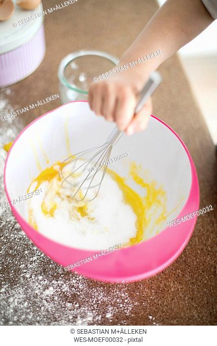 Girl's hand stirring dough