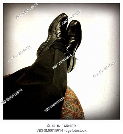 Crossed legs with black dress shoes and pants put up onto a footstool