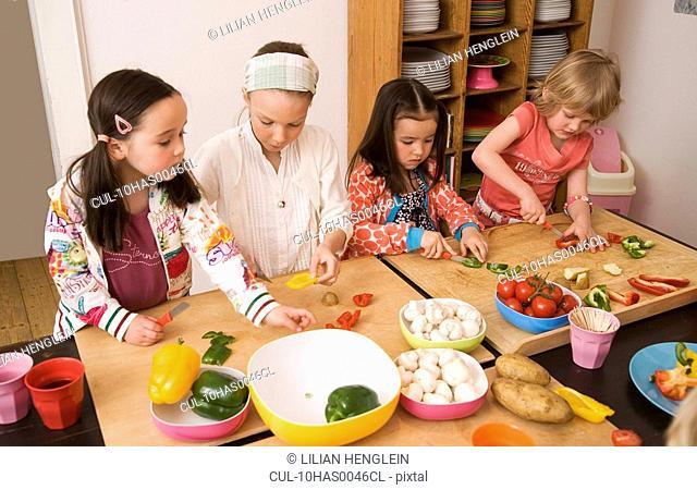 Four girls cutting vegetables