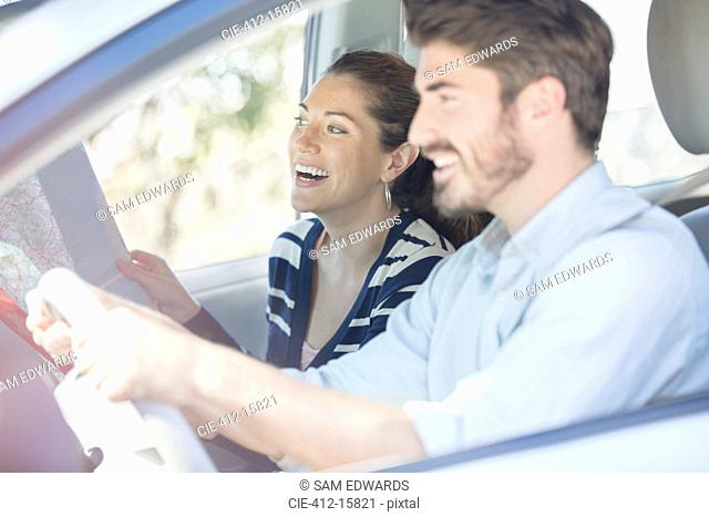 Happy couple with map driving in car