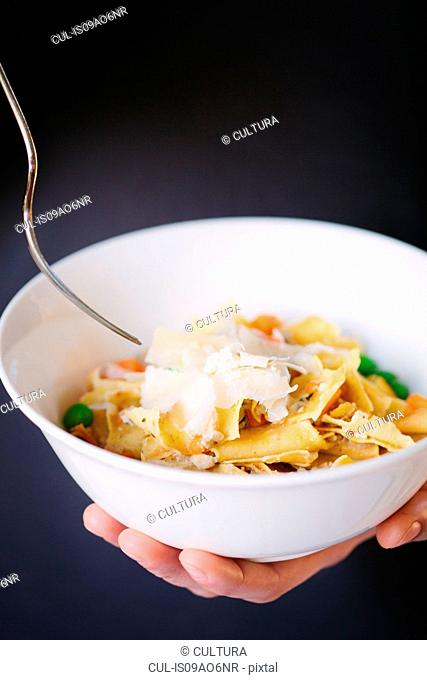 Female hands holding bowl of fresh pasta with carrots, peas and grated cheese