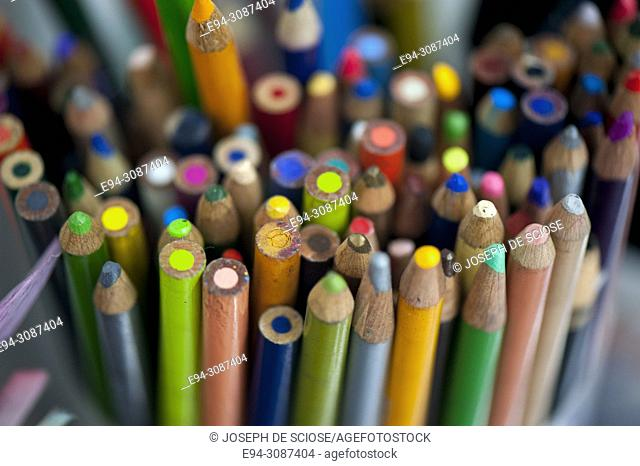 A tight grouping of multi-colored pencils in a container on a desk