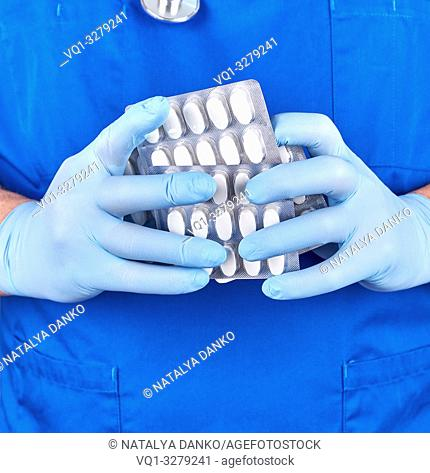 doctor in blue uniform and sterile gloves holding white pills in pack, close up