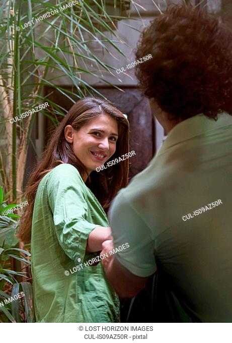 Woman leading young man by the hand smiling