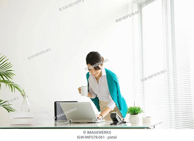 Japan, Osaka Prefecture, Businesswoman with coffee cup using laptop