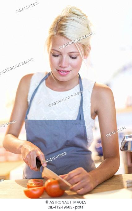 Woman slicing vegetables in kitchen