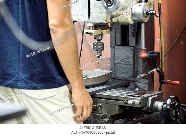 Factory worker using drill
