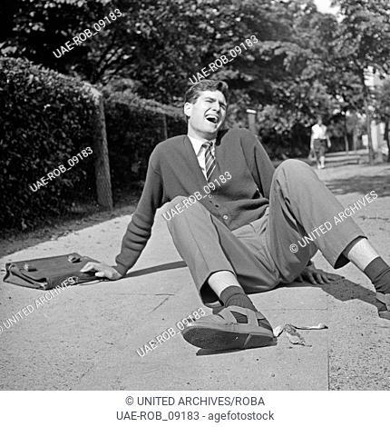 Ein Mann ist in Hamburg auf der Straße auf einer weggeworfenen Bananenschale ausgerutscht, Deutschland 1960er Jahre. A man slipped because a banana peel on the...