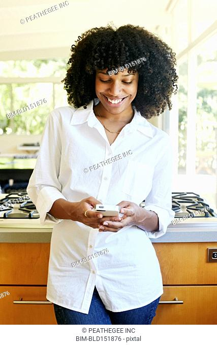 Mixed race woman using cell phone in domestic kitchen