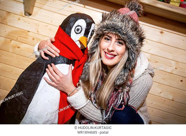Young woman posing with penguin figurine