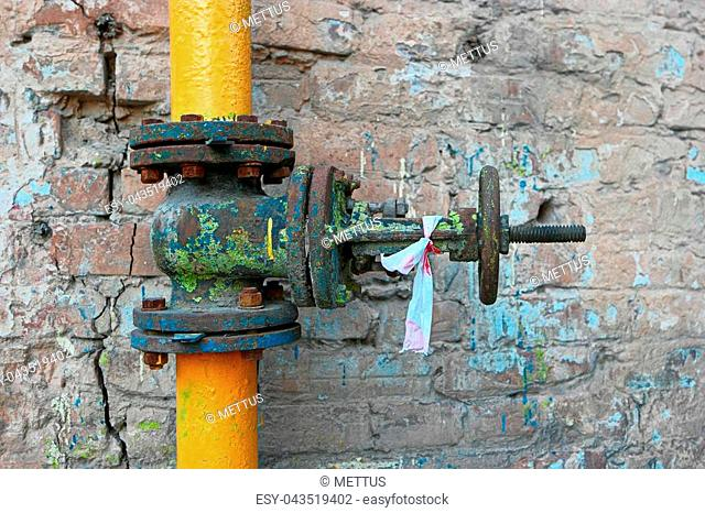 Old gas pipe painted in yellow pipe and rusty valve with spots of obsolete paint at brick wall