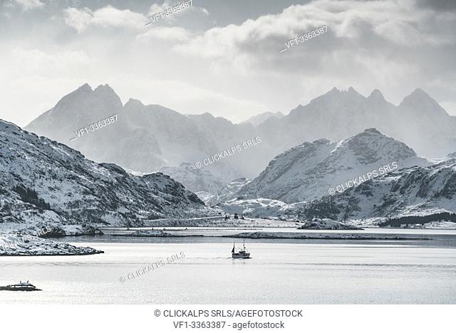 Fishing boat sailing on the fjord, with Tekoppstetten peak in the background in winter. Fredvang, Flakstad municipality, Nordland county, Northern Norway
