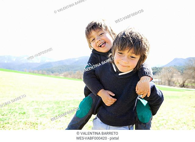 Portrait of little boy carrying his brother piggyback