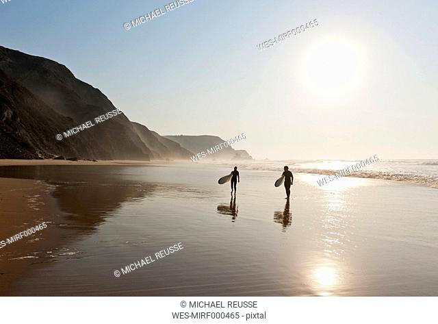 Portugal, Couple walking with surfboard on beach