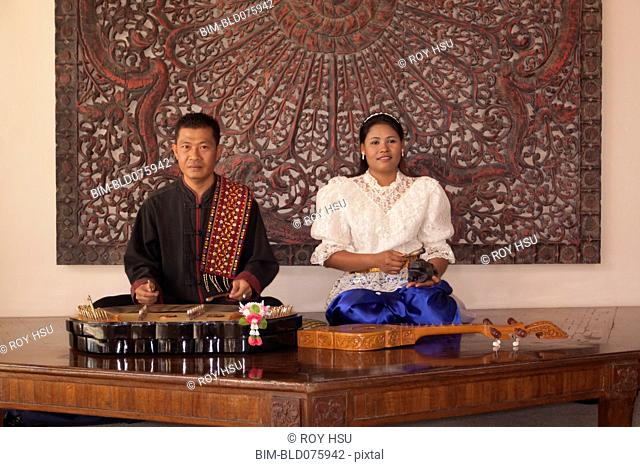 Asian man and woman with traditional musical instruments