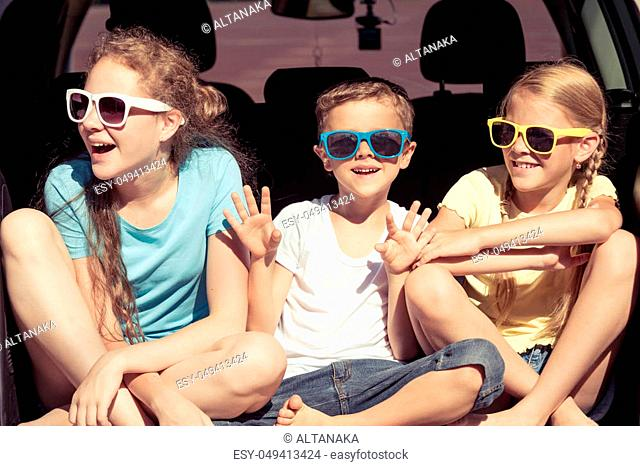 Happy brother and his two sisters are sitting in the car at the day time. Children having fun outdoors. Concept of the family is ready for travel