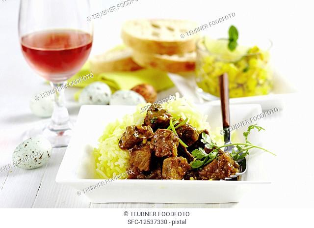 Lamb curry on potato straw served with mango pickles, rose wine and Easter eggs