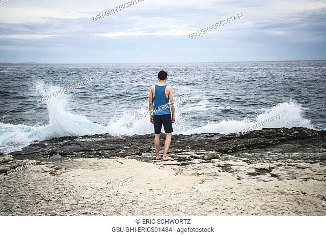 Young Man Watching Waves Against Rocks, Kamenjak National Park, Premantura, Croatia