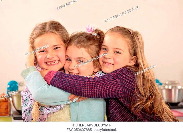 Three little friends hug each other on a couch