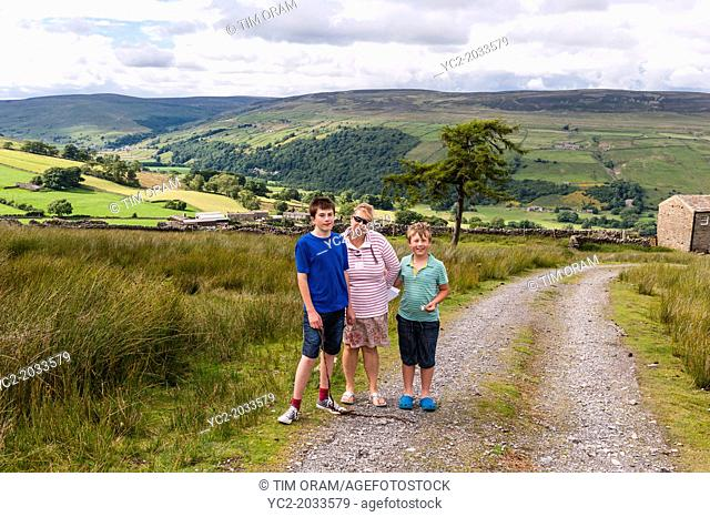 A mother and her 2 sons out on a family walk in Swaledale , North Yorkshire , England , Britain , Uk