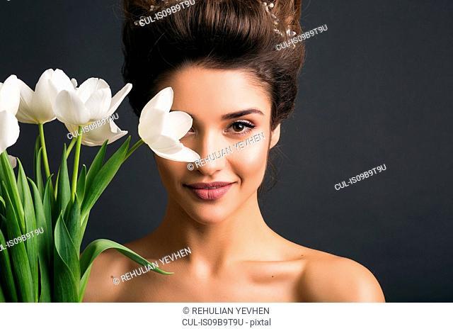 Woman wearing tiara holding tulips