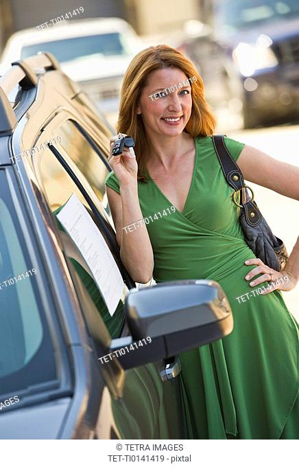 Woman holding car keys for new car
