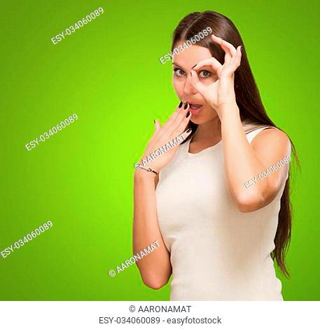 Surprised Young Woman Looking Through Imaginary Binocular against a green background