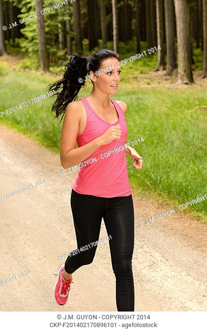 Sportive woman running through forest on summer training day