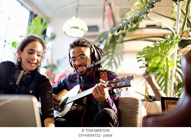 Young man and woman recording music, playing guitar in apartment