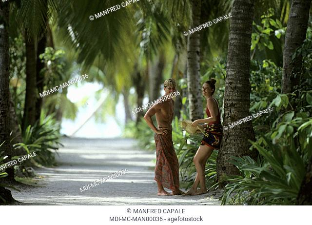Couple standing face to face under trees on the way to the beach