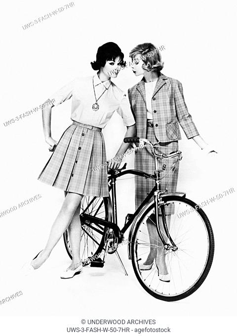 United States: c. 1958 Two women with a bicycle model vacation fashions in cotton for traveling or sightseeing. They are styled by Miss Pat of California