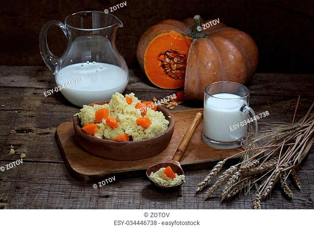 Millet cereal with a pumpkin in a wooden bowl and milk in a jug