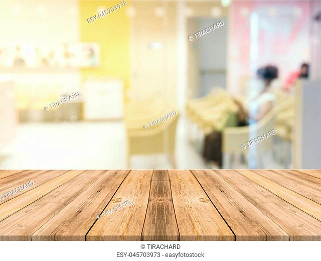 Wooden board empty table in front of blurred background. Perspective brown wood table over blur room in hospital background - can be used mock up for display or...