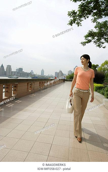 Young woman walking on pavement with shoulder bag