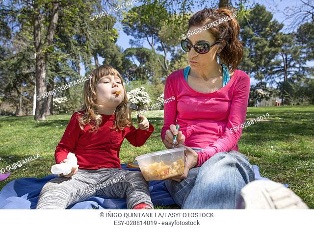 mother and three years old blonde child, sharing and eating pasta salad with fork from plastic container, as picnic, sitting in blue towel on green grass field...
