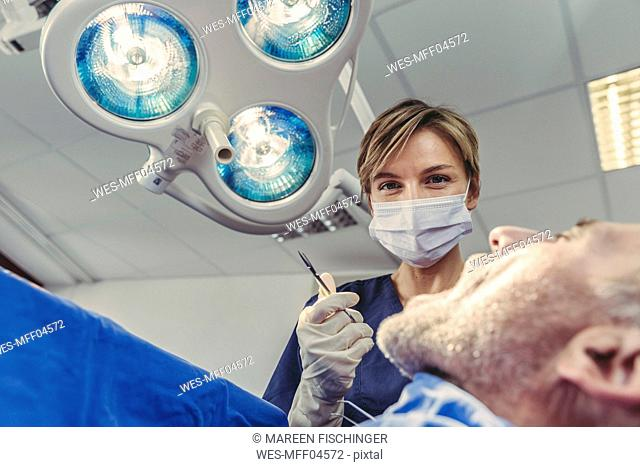 Dental surgeon during surgical procedure on a patient