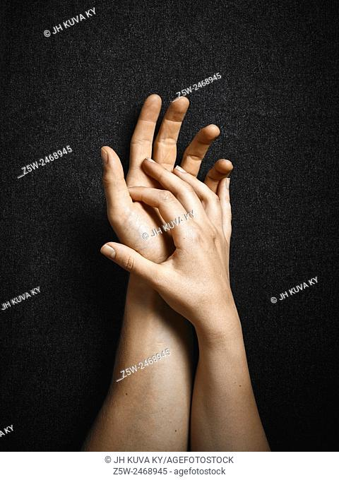 Man and woman, hands connecting together, dark canvas background