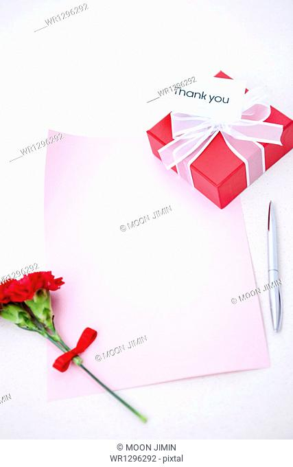 a letter next to a gift box and flower