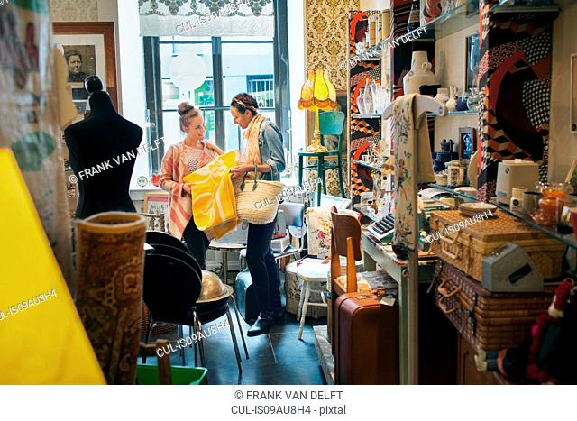Young female customer looking at yellow blanket in vintage shop