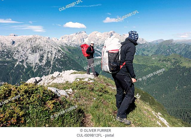 Two wingsuit BASE jumpers walking to the exit spot at Col di Pra, Italian Alps, Alleghe, Belluno, Italy