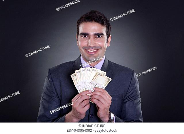 Portrait of businessman holding currency