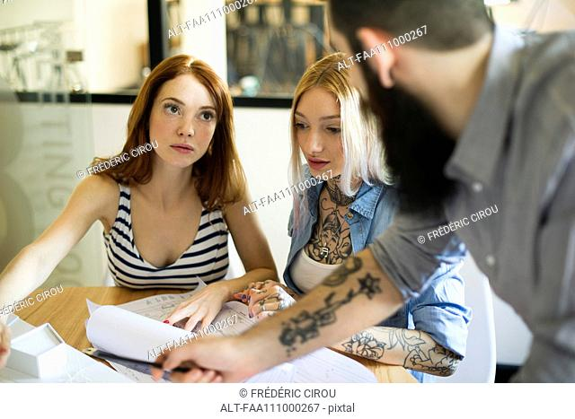 Colleagues discussing blueprints together in casual office