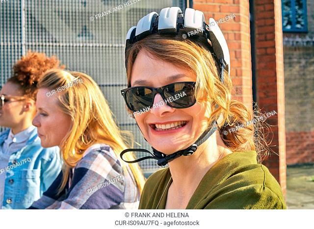Portrait of mature woman wearing sunglasses and bicycle helmet looking at camera smiling