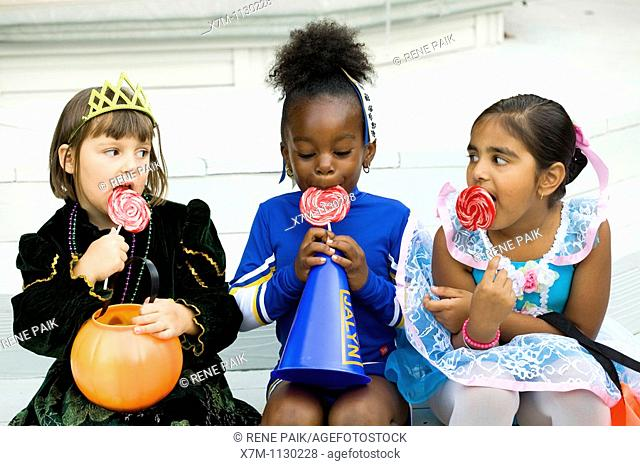 Little girls dressed in Halloween costumes enjoy their lollipops