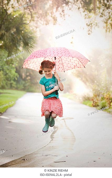 Girl holding up umbrella and jumping puddles on street