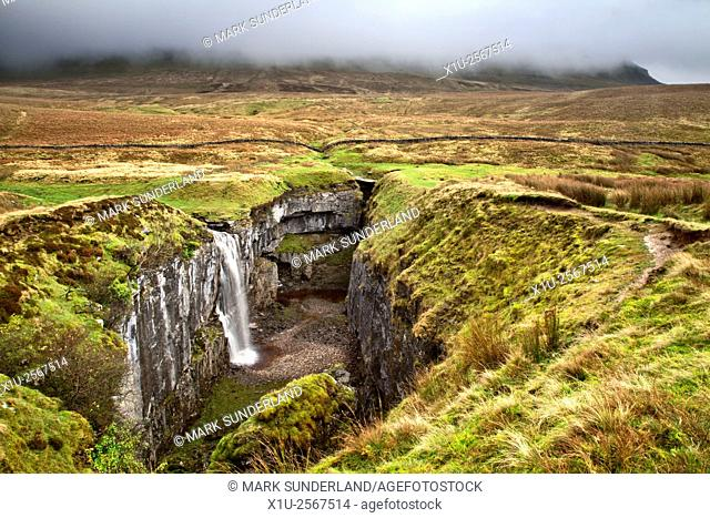 Waterfall at Hull Pot with Pen Y Ghent Shrouded in Low Cloud Horton in Ribblesdale North Yorkshire England
