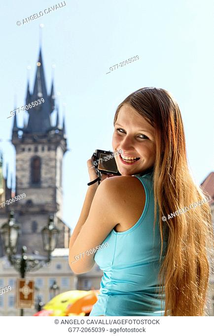 Young woman taking pictures of the Church of Our Lady of Tyn in Prague. Czech Republic. Prague