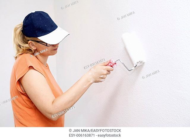 Woman painting white wall with paint roller